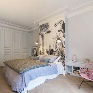 Cette photo montre une chambre éclectique avec un mur gris, un sol en bois clair et un sol beige.