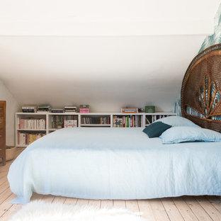 Exemple d'une petite chambre exotique avec un sol en bois clair, un sol beige et un mur blanc.