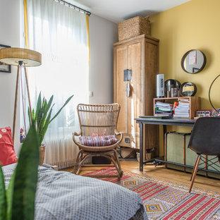 Cette photo montre une chambre éclectique avec un mur jaune, un sol en bois brun et un sol marron.