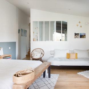 Cette photo montre une chambre parentale scandinave avec un mur blanc, un sol en bois clair, aucune cheminée et un sol beige.