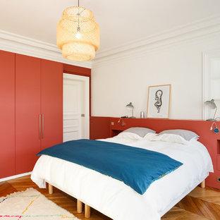 Idée de décoration pour une grand chambre parentale minimaliste avec un mur rouge, un sol en bois brun, aucune cheminée et un sol marron.