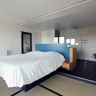 Idée de décoration pour une grande chambre parentale design avec un mur blanc.