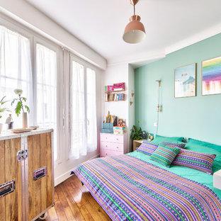 Idées déco pour une chambre contemporaine de taille moyenne avec un mur vert, un sol en bois clair et un sol beige.