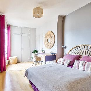 Aménagement d'une chambre d'amis contemporaine avec un mur blanc, un sol en bois clair et un sol beige.
