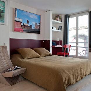 Réalisation d'une chambre adulte design de taille moyenne avec un mur blanc et un sol en bois clair.