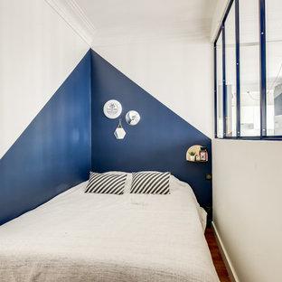 Exemple d'une chambre tendance avec un mur bleu et un sol en bois brun.