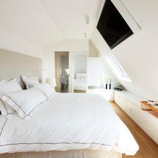 Inspiration pour une chambre design de taille moyenne avec un mur blanc et un sol en bois brun.