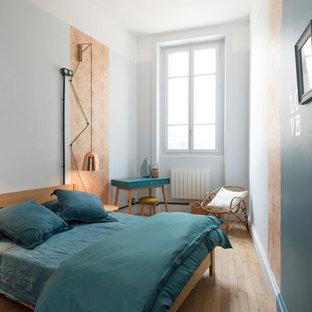 Idée de décoration pour une chambre d'amis nordique avec un mur multicolore, un sol en bois clair et un sol beige.