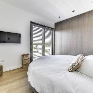 Cette image montre une chambre design avec un mur blanc, un sol en bois clair et un sol beige.