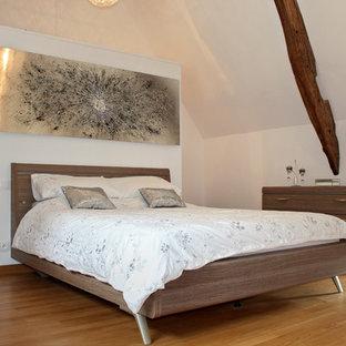 Réalisation d'une chambre parentale champêtre avec un mur blanc, un sol en bois brun et un sol marron.