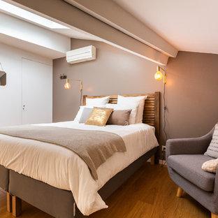 Cette photo montre une chambre chic avec un mur beige, un sol en bois brun et un sol marron.