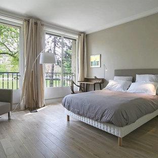 Idée de décoration pour une chambre parentale tradition de taille moyenne avec un sol en bois clair, un mur gris et aucune cheminée.