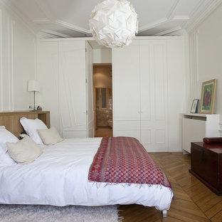 Idée de décoration pour une chambre tradition avec un mur blanc, un sol en bois brun et un sol marron.