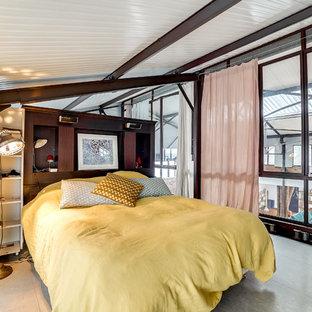 Aménagement d'une grand chambre mansardée ou avec mezzanine industrielle avec un sol gris.