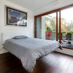 Idée de décoration pour une chambre design avec un mur blanc et un sol en bois foncé.