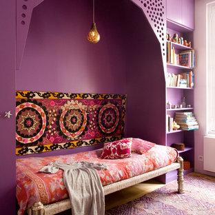 Réalisation d'une chambre parentale bohème avec un mur violet, un sol en bois clair et aucune cheminée.