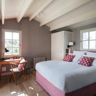 Inspiration pour une chambre traditionnelle de taille moyenne avec un mur gris et un sol en bois brun.
