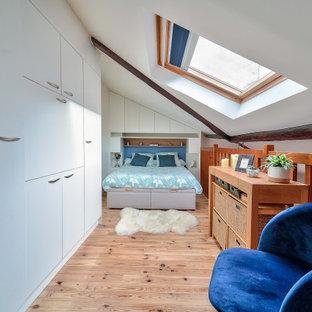 Cette photo montre une chambre mansardée ou avec mezzanine tendance avec un mur blanc, un sol en bois clair, un sol beige et un plafond voûté.