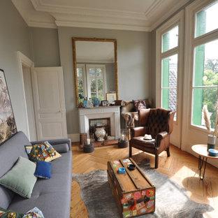 Ejemplo de dormitorio tipo loft, bohemio, de tamaño medio, con paredes grises, suelo de madera oscura, chimenea tradicional, marco de chimenea de ladrillo y suelo marrón