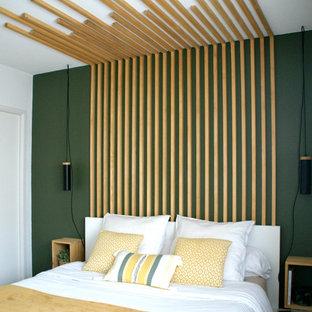 Cette photo montre une petit chambre parentale scandinave avec un mur vert, un sol en bois clair, aucune cheminée et un sol beige.