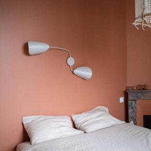 Imagen de habitación de invitados actual, pequeña, con parades naranjas, suelo de madera clara, chimenea de esquina y marco de chimenea de piedra
