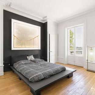 Idée de décoration pour une chambre parentale tradition avec un mur noir et un sol en bois clair.