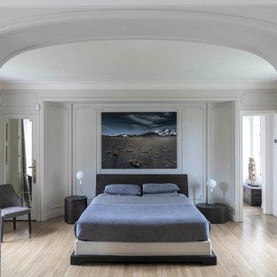 Cette photo montre une grande chambre parentale éclectique avec un mur blanc, un sol en bois clair, un sol beige et aucune cheminée.