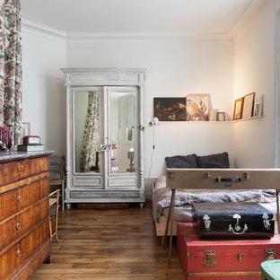 Cette photo montre une chambre éclectique avec un mur blanc et un sol en bois brun.