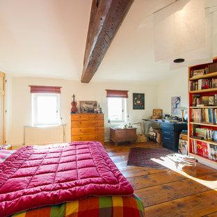 Cette photo montre une chambre parentale nature avec un mur beige et un sol en bois foncé.