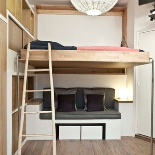 Photo of a small contemporary mezzanine bedroom in Paris with white walls, medium hardwood flooring and no fireplace.
