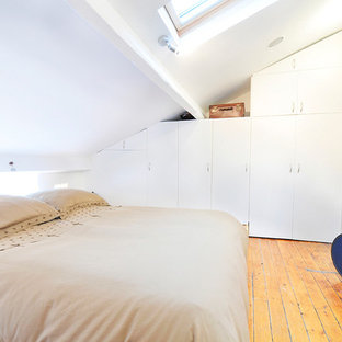 Photo of a small contemporary bedroom in Paris with white walls, light hardwood floors and no fireplace.