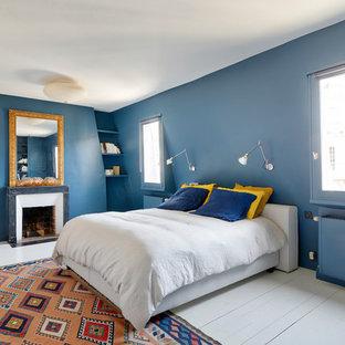 Modelo de dormitorio principal, bohemio, con paredes azules, suelo de madera pintada, chimenea tradicional, marco de chimenea de ladrillo y suelo blanco