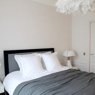 Réalisation d'une chambre d'amis bohème avec un mur blanc, un sol en bois foncé et un sol marron.