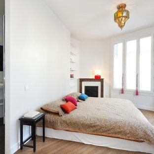 Réalisation d'une chambre bohème avec un mur blanc, un sol en bois brun et une cheminée d'angle.
