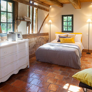 Design ideas for a mid-sized country guest bedroom in Le Havre with white walls and terra-cotta floors.