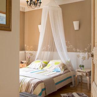 Aménagement d'une chambre parentale classique de taille moyenne avec un mur multicolore, un sol en bois brun et aucune cheminée.