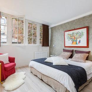 Inspiration pour une chambre d'amis bohème avec un mur blanc, un sol en bois clair et un sol beige.