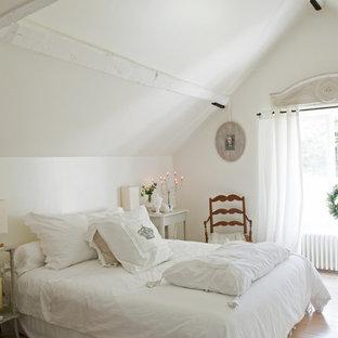 Ejemplo de dormitorio romántico con paredes blancas y suelo de madera clara