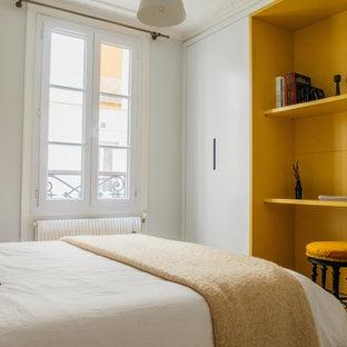 Cette image montre une petit chambre d'amis design avec un mur gris, un sol en bois brun et un sol beige.