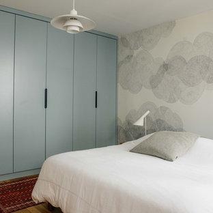 パリの中サイズのコンテンポラリースタイルのおしゃれな主寝室 (グレーの壁、淡色無垢フローリング、標準型暖炉、金属の暖炉まわり) のインテリア