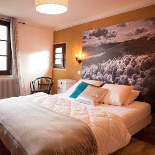 Diseño de dormitorio principal, urbano, de tamaño medio, sin chimenea, con paredes amarillas, suelo de madera clara y suelo marrón