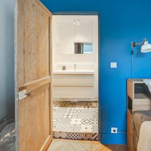 Foto de dormitorio nórdico con paredes azules, suelo de madera en tonos medios, chimenea de doble cara y suelo marrón