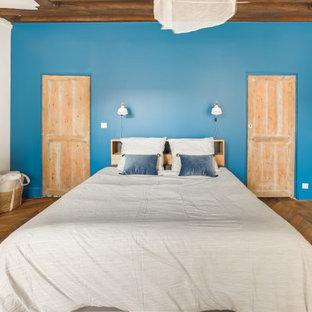 Modelo de dormitorio nórdico con paredes azules, suelo de madera en tonos medios, chimenea de doble cara y suelo marrón