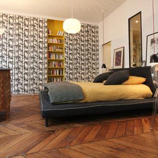 Exemple d'une grande chambre parentale tendance avec un mur multicolore et un sol en bois brun.