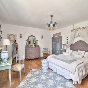 Design ideas for a traditional master bedroom in Paris with white walls, terra-cotta floors and no fireplace.