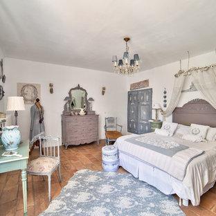 Idée de décoration pour une chambre parentale style shabby chic avec un mur blanc, un sol en carreau de terre cuite et aucune cheminée.
