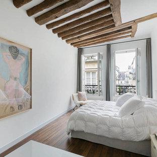 Aménagement d'une chambre contemporaine avec un mur blanc et un sol en bois brun.
