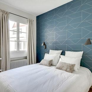 Modelo de habitación de invitados escandinava con paredes azules, suelo de madera clara y suelo beige