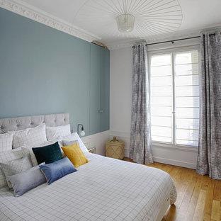 Idées déco pour une chambre contemporaine avec un mur bleu, un sol en bois brun et un sol marron.