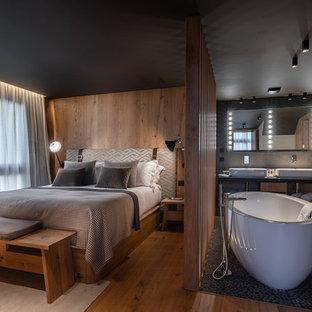 Idée de décoration pour une chambre parentale chalet avec un mur marron, un sol en bois brun et un sol marron.